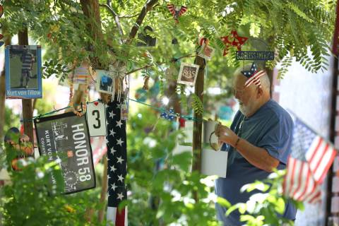Michael Hyatt, 67, decorates his brother-in-law's tree, Kurt Von Tillow, who was killed during ...