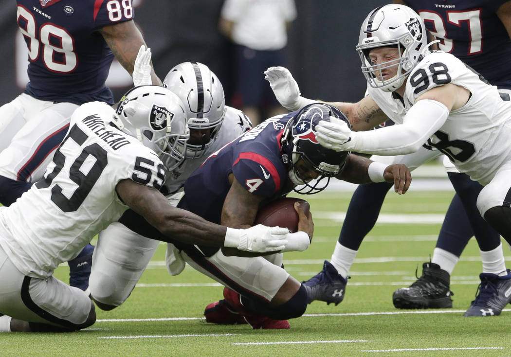 Houston Texans quarterback Deshaun Watson (4) is hit by Oakland Raiders defenders Tahir Whitehe ...