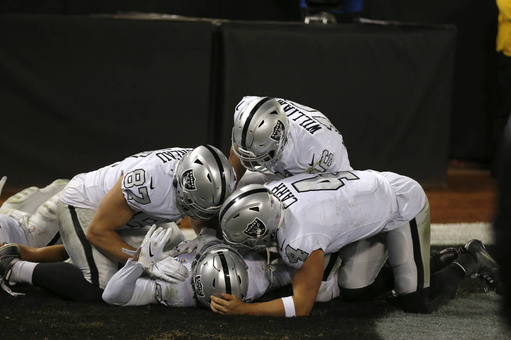 Oakland Raiders running back Josh Jacobs, bottom, celebrates with teammates after scoring again ...