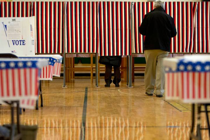 People cast their votes in the presidential primary at Windham High School in Windham, N.H., Tu ...