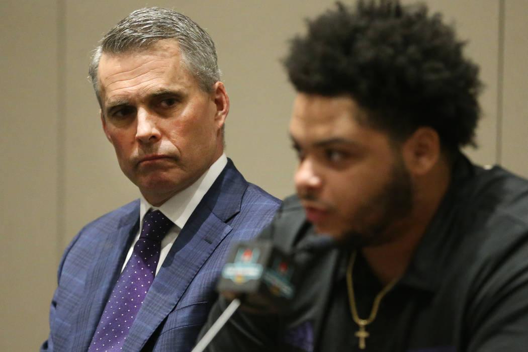 Washington Huskies head coach Chris Petersen, left, looks on at offensive lineman Nick Harris s ...