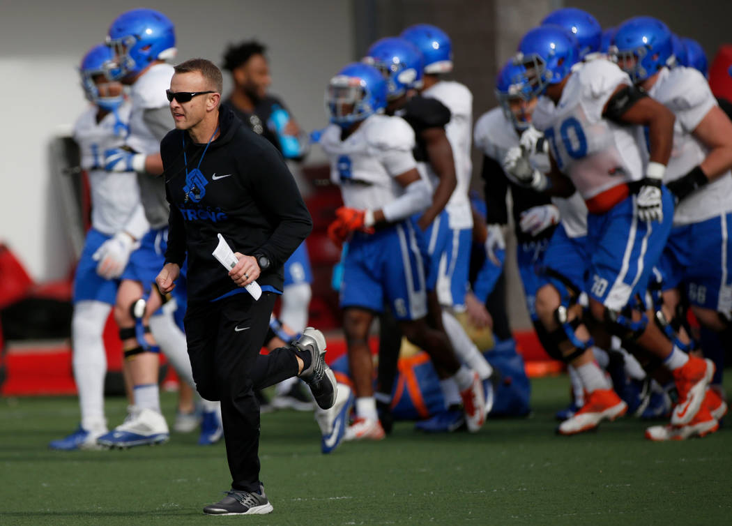 Boise State head coach Bryan Harsin, left, runs with his players during football practice in La ...