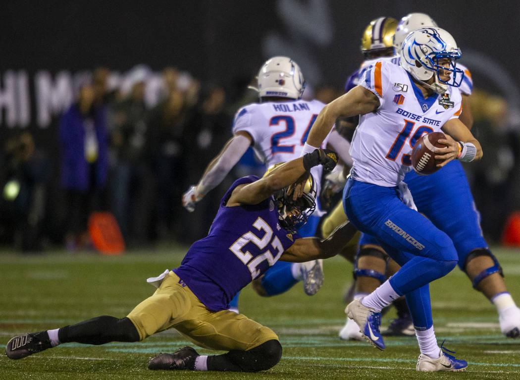 Boise State Broncos quarterback Hank Bachmeier (19, right) slips a near sack by Washington Husk ...