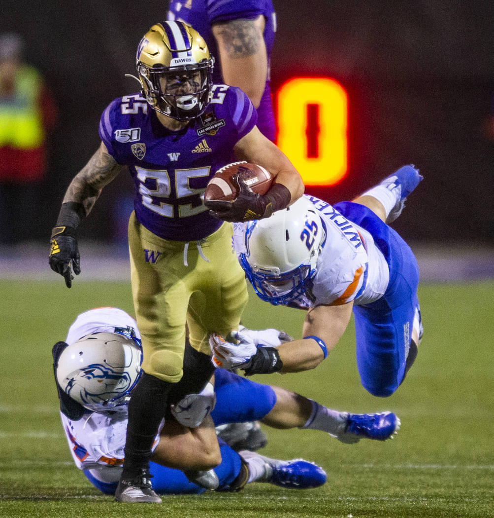 Washington Huskies running back Sean McGrew (25, top) attempts to break a tackle from Boise Sta ...