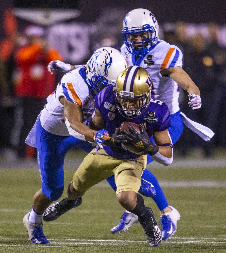 Washington Huskies wide receiver Andre Baccellia (5, front) is finally taken down by Boise Stat ...