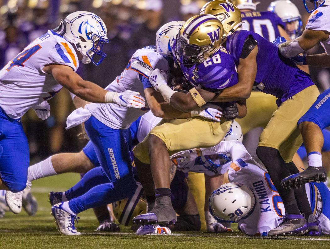 Washington Huskies running back Richard Newton (28, center) is stopped by Boise State Broncos w ...