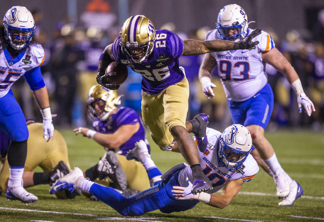 Washington Huskies running back Salvon Ahmed (26, tops) breaks free from a diving tackle attemp ...