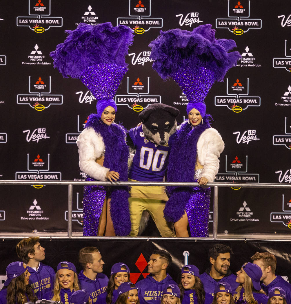Washington Huskies mascot Harry the Husky poses with two showgirls after defeating the Boise St ...