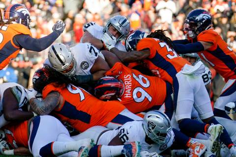 Oakland Raiders running back Alec Ingold, above center, is stopped before the goal line during ...