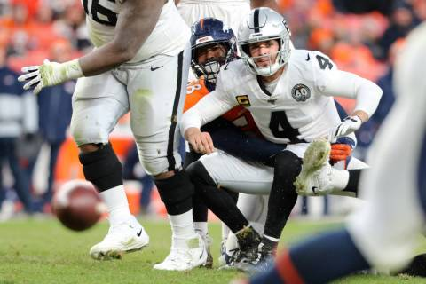 Oakland Raiders quarterback Derek Carr (4) looks at his pass fall incomplete as he is tackled b ...