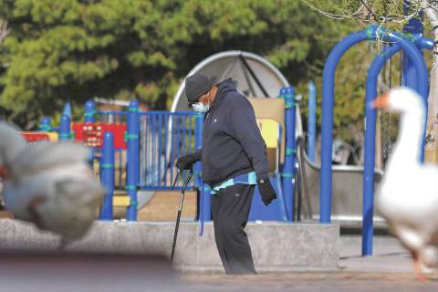 A man, who declined to give his name, wears protective masks as he walks at Sunset Park on Wedn ...