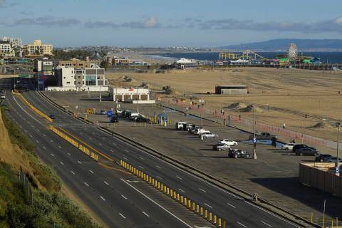 Light traffic and a mostly empty parking lot is seen along Pacific Coast Highway, Monday, March ...