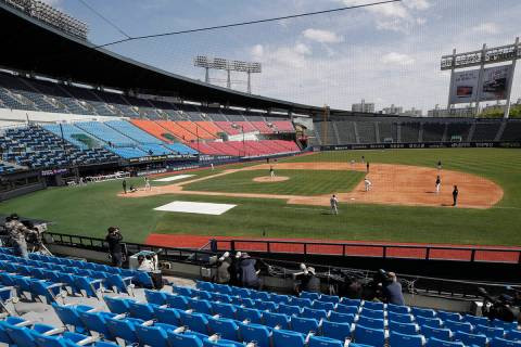 Photographers and TV camera work near empty seats during the pre-season baseball game between D ...