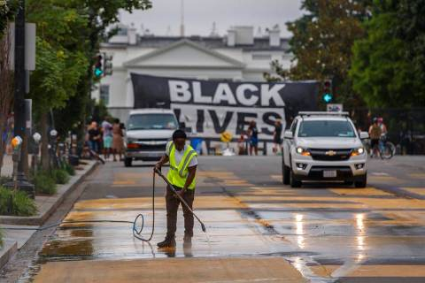 A city worker cleans the words Black Lives Matter painted in bright yellow letters on 16th Stre ...