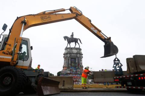 Workers for The Virginia Department of General Services install concrete barriers around the st ...