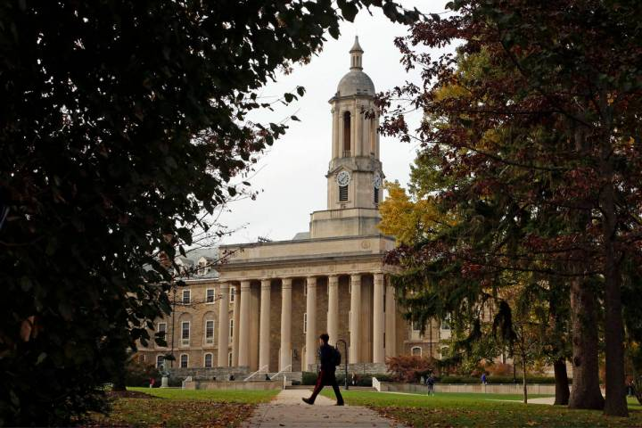 FILE- In this Nov. 9, 2017, file photo people walk by Old Main on the Penn State University mai ...