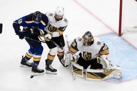 St. Louis Blues' Zach Sanford (12) and Vegas Golden Knights' Shea Theodore (27) battle in front ...