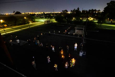 People gather in the shape of the trans symbol during a candlelight vigil, in remembrance of th ...