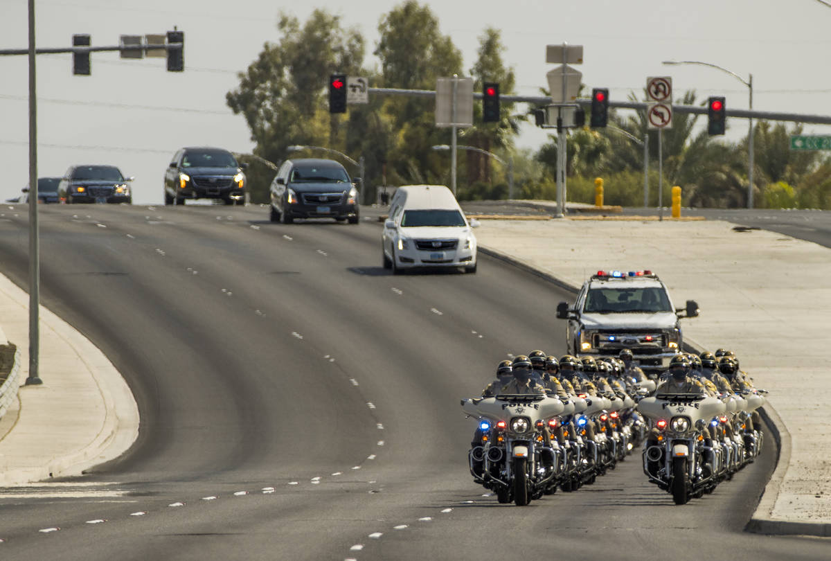 Metro motorcycle officers lead a white hearse arriving for a burial service for Metro Lt. Erik ...