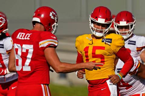 Kansas City Chiefs quarterback Patrick Mahomes (15) and tight end Travis Kelce (87) talk during ...