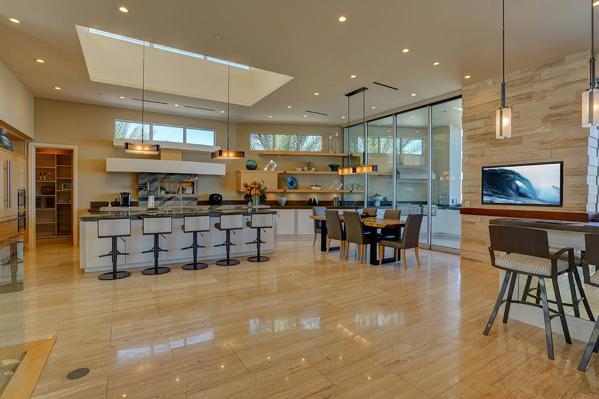 The large kitchen has a seamless transition to the massive outdoor kitchen and patio, which fea ...