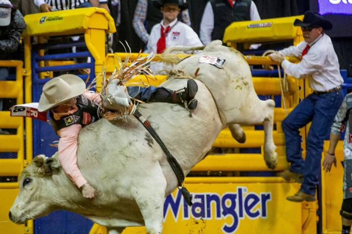 Clayton Sellars of Fruitland Park, Fla., clings to his ride in Bull Riding at the tenth go roun ...