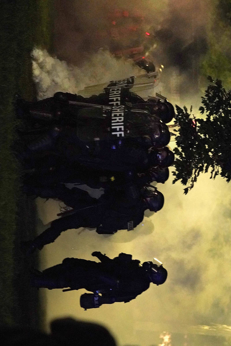 Police in riot gear clear a park during clashes with protesters outside the Kenosha County Cour ...