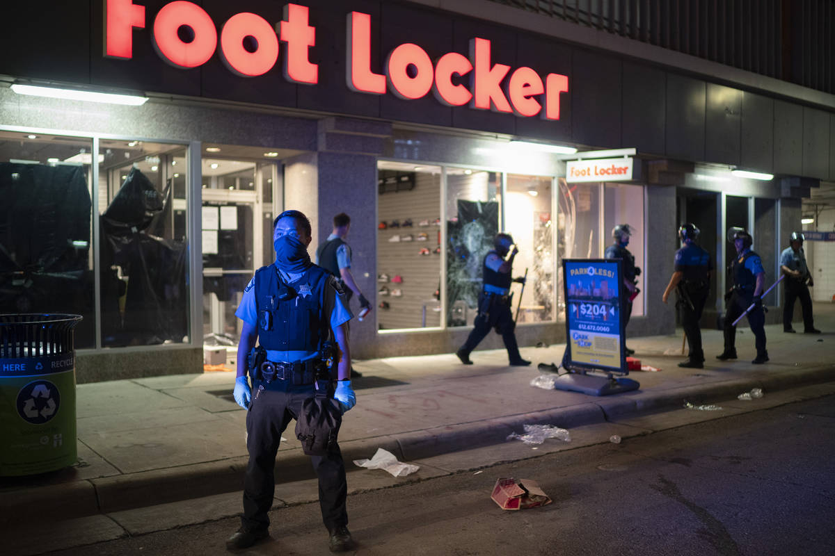 Minneapolis Police stand outside a looted Foot Locker store on S. 7th St., Wednesday, Aug. 26, ...