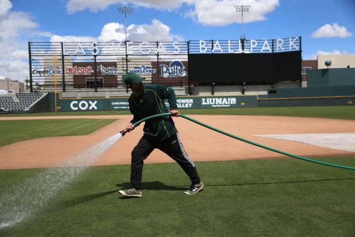 Groundskeeper Logan Mace sprays water on the field at the Las Vegas Ballpark in Las Vegas, Thur ...