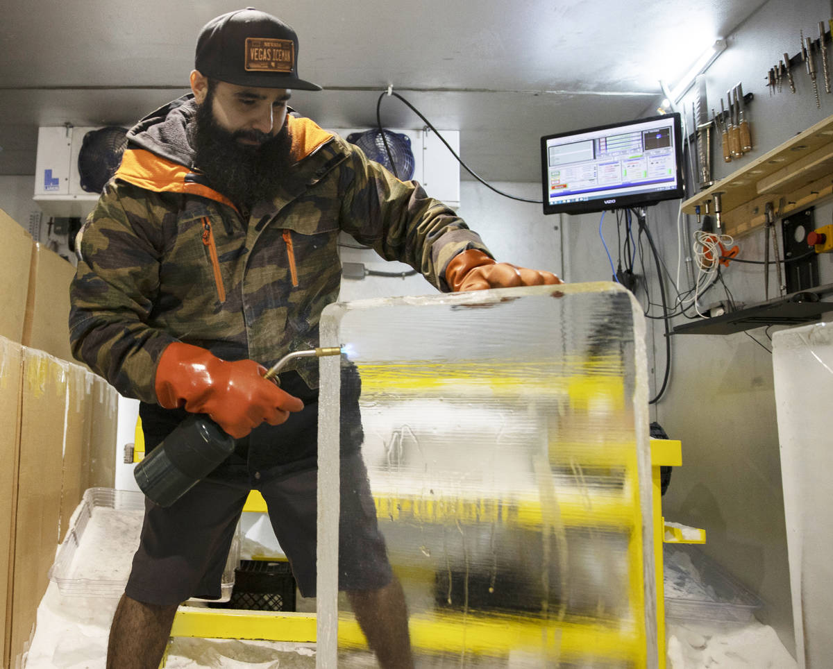 "Marco Villarreal, known as ""Vegas Ice Man,"" uses a torch to prep a fresh ice block on ..."