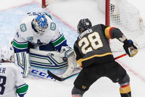 Vancouver Canucks goalie Thatcher Demko (35) makes a save on Vegas Golden Knights' William Carr ...