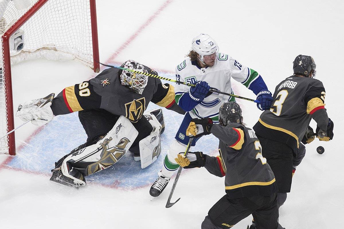Vancouver Canucks' Tyler Toffoli (73) and Vegas Golden Knights' Zach Whitecloud (2) and Brayden ...