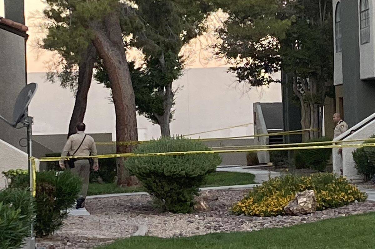 Officers stand guard outside the scene of a homicide investigation at Sunset Cove Apartments, 5 ...