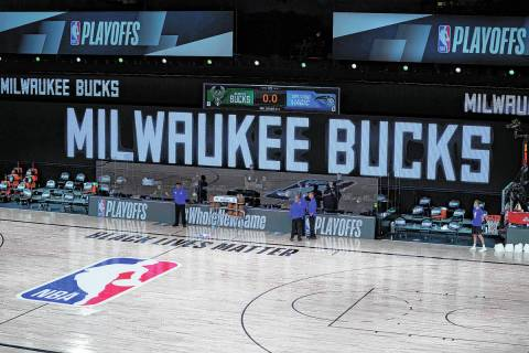 Officials stand beside an empty court at the scheduled start of an NBA basketball first round p ...