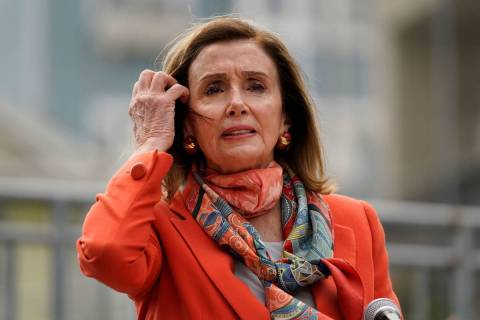 House Speaker Nancy Pelosi pulls back her hair while speaking about her visit to a hair salon d ...