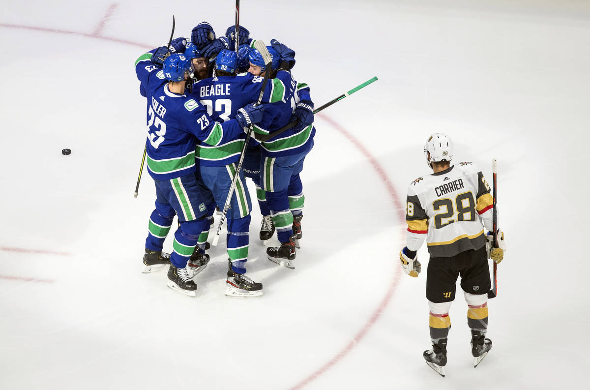 Vancouver Canucks players celebrate a goal as Vegas Golden Knights William Carrier (28) looks o ...