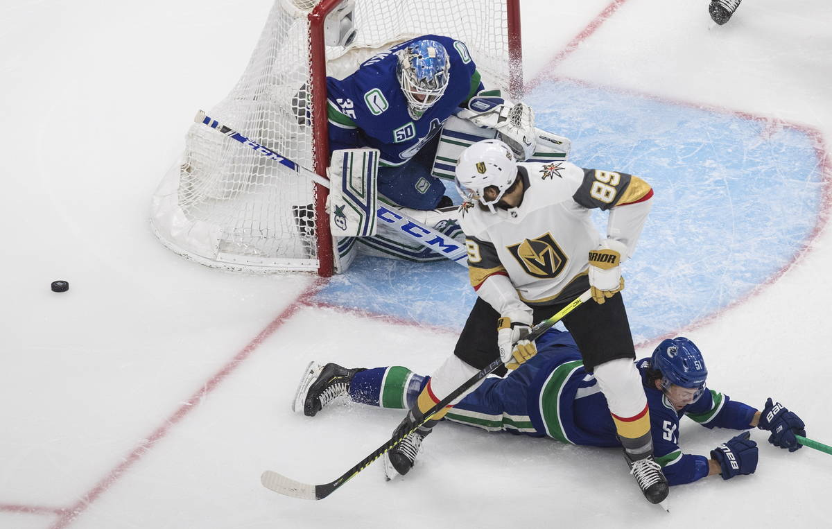 Vancouver Canucks goalie Thatcher Demko (35) makes a save on Vegas Golden Knights' Alex Tuch (8 ...