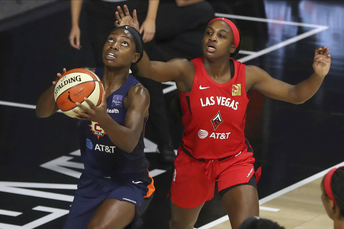 Connecticut Sun's Kaila Charles, left, drives past Las Vegas Aces' Jackie Young during the firs ...