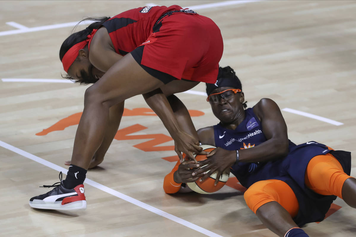 Connecticut Sun's Essence Carson, right, reaches for a ball underneath Las Vegas Aces' Jackie Y ...