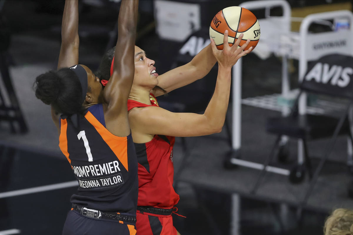 Las Vegas Aces' Dearica Hamby, right, drives past Connecticut Sun's Beatrice Mompremier during ...