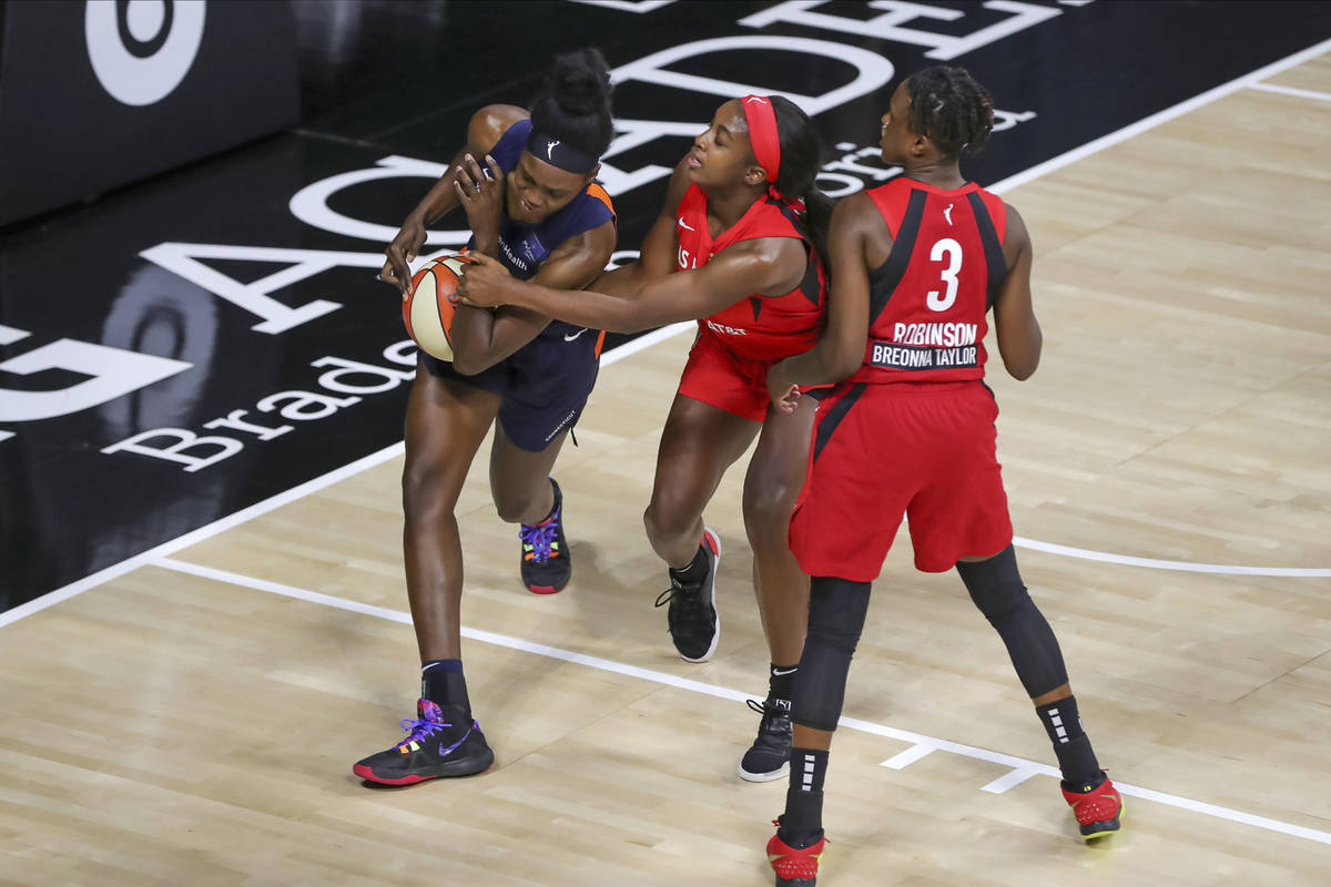 Connecticut Sun's Beatrice Mompremier, left, is stripped of the ball by Las Vegas Aces' Jackie ...