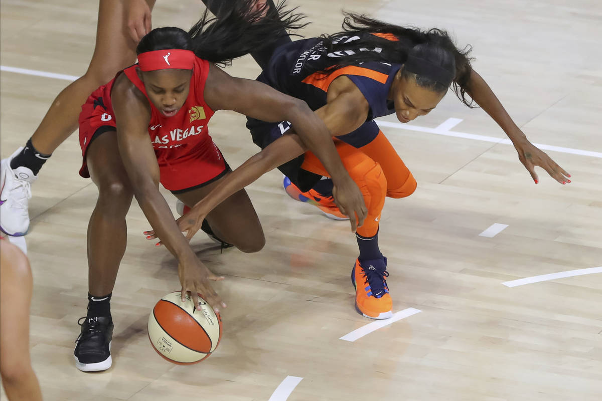 Las Vegas Aces' Jackie Young, left, and Connecticut Sun's DeWanna Bonner reach for the ball dur ...