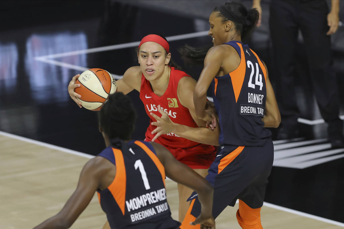 Las Vegas Aces' Dearica Hamby, center, drives against Connecticut Sun's DeWanna Bonner (24) and ...