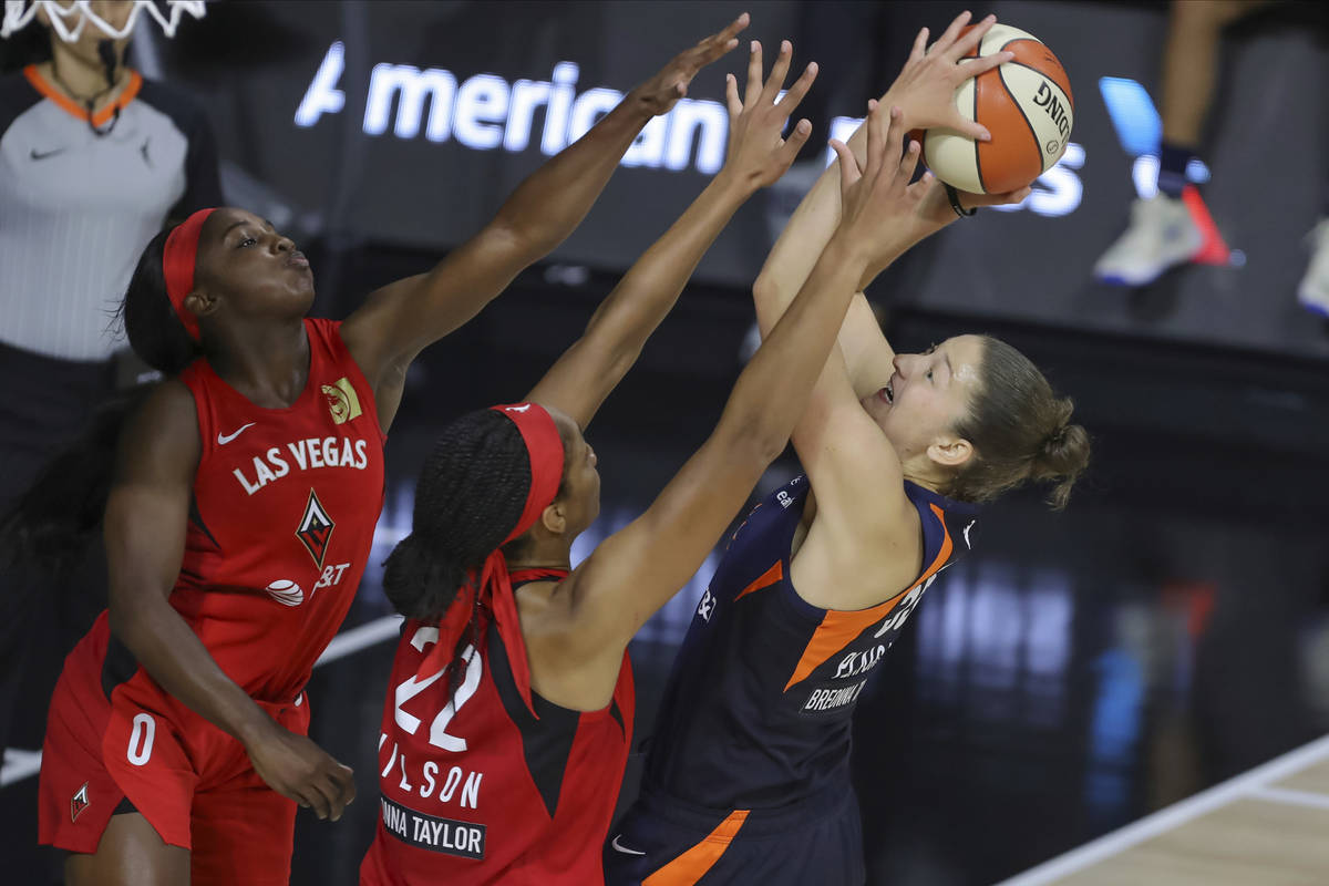 Connecticut Sun's Theresa Plaisance, right, shoots ovr Las Vegas Aces' Jackie Young (0) and A'j ...