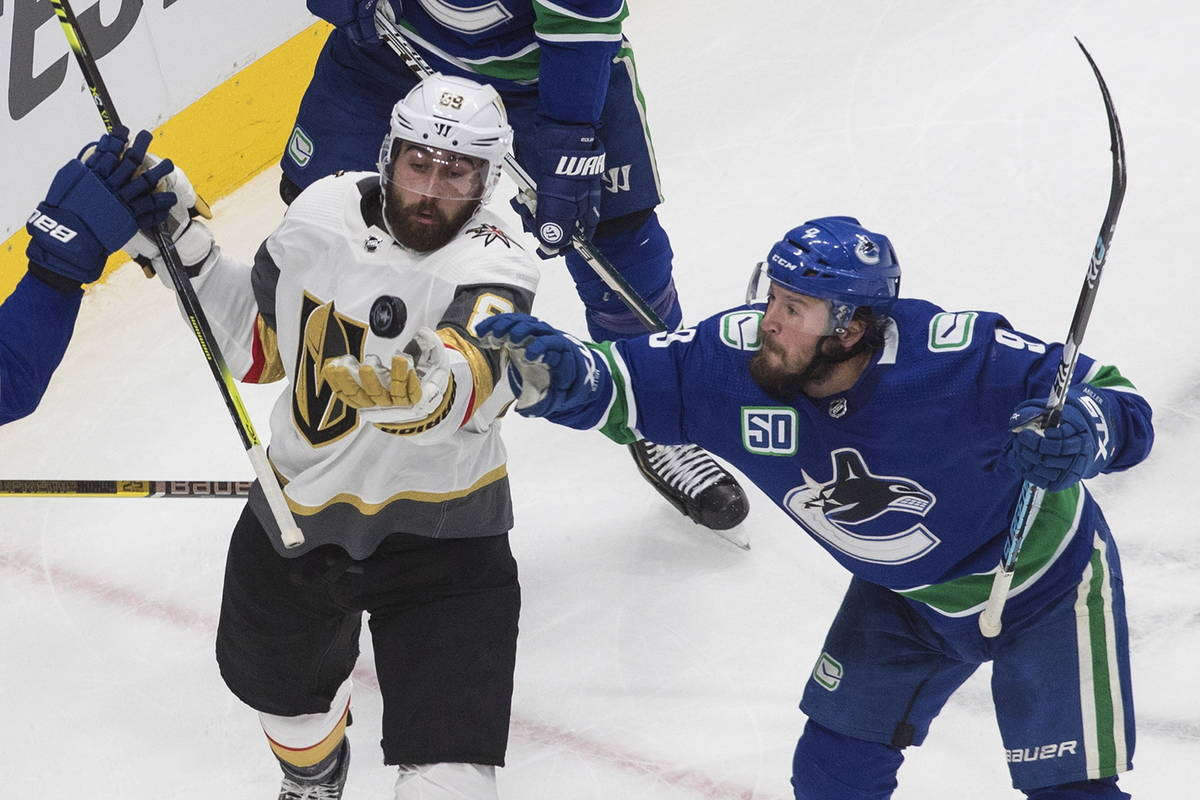 Vancouver Canucks' J.T. Miller (9) and Vegas Golden Knights' Alex Tuch (89) reach for the puck ...