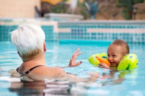 King Carter, 1, sprays his grandma, Tina Carter, with a squirt gun in their backyard pool on Su ...