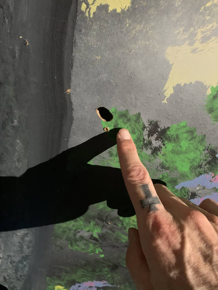 Zak Bagans points to a bullet hole at the scene of Travis Maldonado's suicide at Greater Wynnew ...