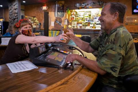 Bartender Teah Heath, left, serves a beer to Lyle Bogggess at Jackson's Bar & Grill on Thursd ...