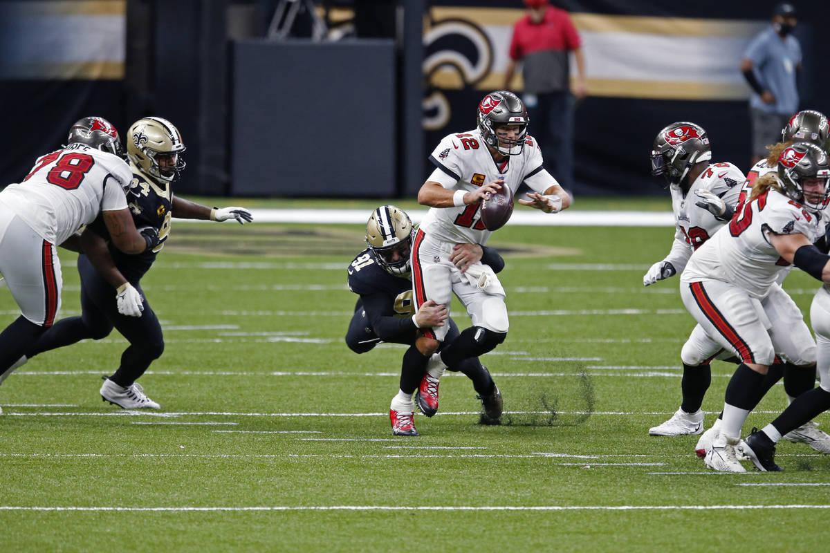 Tampa Bay Buccaneers quarterback Tom Brady (12) scrambles under pressure from New Orleans Saint ...