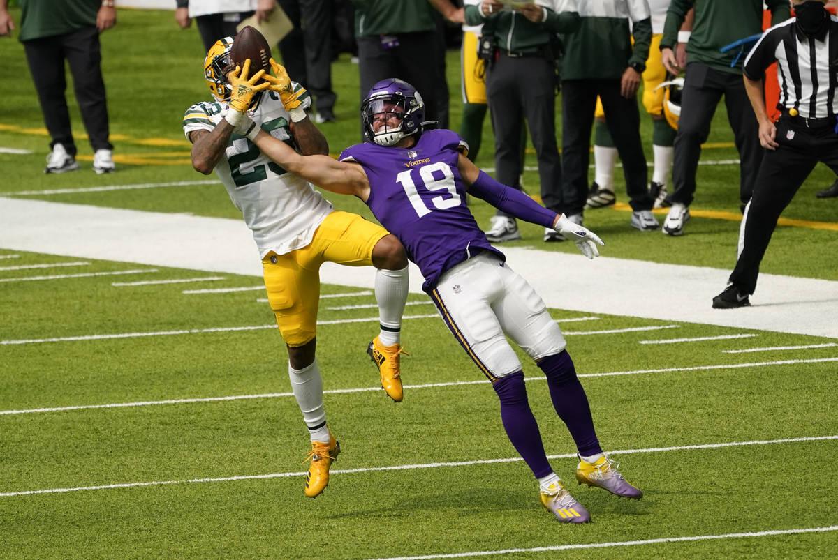 Green Bay Packers cornerback Jaire Alexander, left, intercepts a pass intended for Minnesota Vi ...